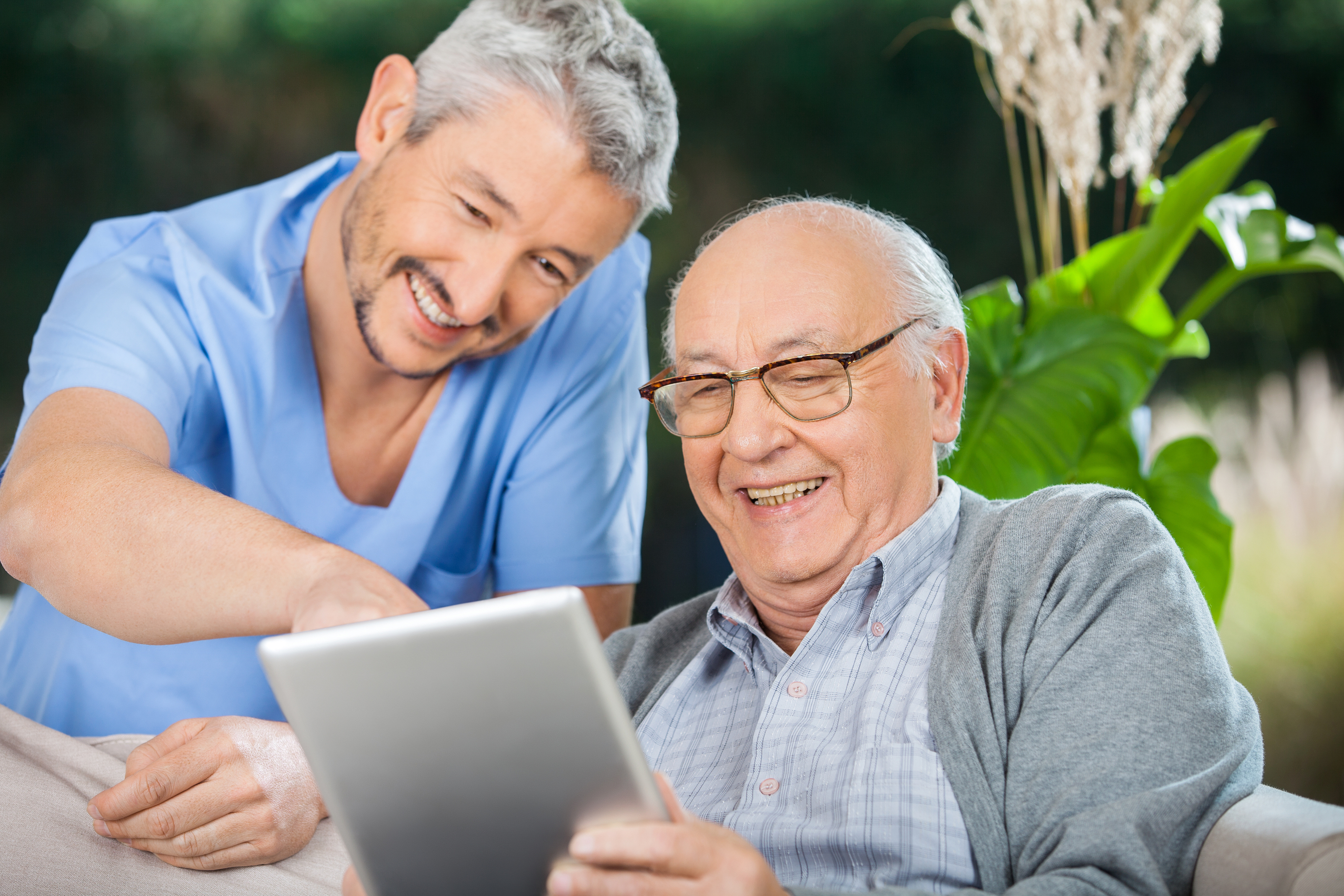 Happy male nurse and senior man enjoying while using tablet in Glendale, CA